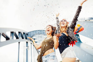 Two young women throwing confetti into the air and looking up,